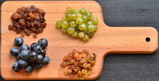 Various raisins, vine berries and almonds on chopping board Stock Photos