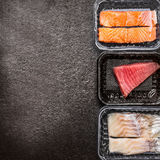 Various of raw fish fillets : salmon, tuna and codfish in plastic boxes on dark rustic background, top view, border, place for tex. T. Healthy Seafood concept Royalty Free Stock Image