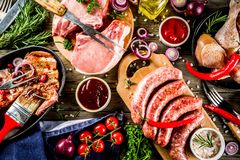 Various raw meat ready for grill and bbq. With vegetables, greens, sauces kitchen grilling utensils. Chicken legs, pork steaks, sausages, beef ribs with herbs royalty free stock photo