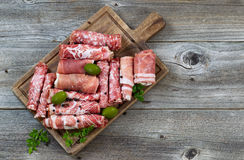 Various raw meats on rustic serving board Royalty Free Stock Photo