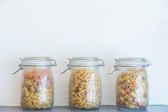 Various raw pasta. Glass jar Royalty Free Stock Images