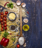 Various raw pasta with vegetables and spices, flour and wooden spoon frame with text area  wooden rustic background top view Royalty Free Stock Photos