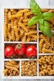 Various raw wholegrain pasta in white wooden box Stock Photos