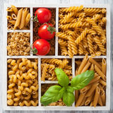Various raw wholegrain pasta in white wooden box Stock Images