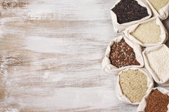 Various rice in bags. Set of various rice in canvas bugs on wooden background: white glutinous, black, basmati, brown and thai red mixed rice. Top view Stock Image