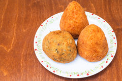 Various rice balls arancini on plate on table. Traditional sicilian street food - various rice balls arancini on plate on table Stock Photo