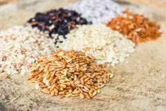 Various rice types each within an individual pile on rustic wood Stock Photography