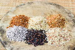 Various rice types each within an individual pile on rustic wood Stock Photos