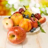 Various ripe fruits on a plate on a blurred background Stock Photo