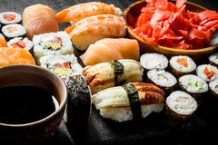 Various rolls, sushi and maki on a stone Board with soy sauce and ginger. On dark rustic background stock photo