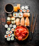 Various rolls, sushi and maki on a stone Board with soy sauce and ginger. On dark rustic background royalty free stock photo