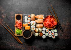 Various rolls, sushi and maki on a stone Board with soy sauce and ginger. On dark rustic background royalty free stock image