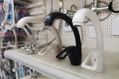 Various samples of mixers and sanitary products on the counter. Modern kitchenware water faucets in the store. Sales stock photos