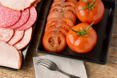 Various sausages and tomatoes Royalty Free Stock Photos