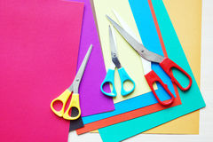 Various scissors lie on sheets of varicolored paper Stock Images