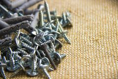 Various screws with dowels and screws lined on burlap. Many screws background. Work tools close up. stock photo