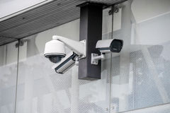 Various security cameras at office glass building exterior Stock Images
