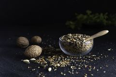 Various seeds in a glass bowl on dark background stock photography