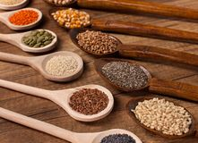 Various seeds and grains in wooden spoons royalty free stock image