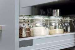 Various seeds in storage jars in hutch, white modern kitchen in background. Smart kitchen organization royalty free stock photos