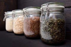 Various seeds in storage jars in pantry, dark wooden background. Smart kitchen organization royalty free stock photos