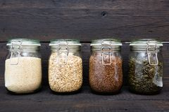 Various seeds in storage jars in pantry, dark wooden background. Smart kitchen organization royalty free stock photography
