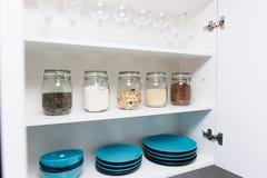 Various seeds in storage jars in pantry, white modern kitchen in background. Smart kitchen organization stock photos