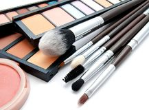 Various set of professional makeup brushes and palette of colourful eye shadows isolated. Over white background stock photography