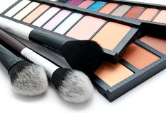 Various set of professional makeup brushes and palette of colourful eye shadows isolated. Over white background royalty free stock images