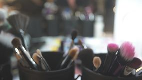Cosmetic Brushes in Cup. Various sets of cosmetic brushes in black cups on the table against blurred background stock video