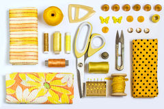 Various sewing accessories and tools yellow shades Royalty Free Stock Photos