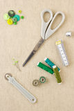 Sewing accessories in green tones. Various sewing items, including scissors, tailors wheel, bobbins, spools of thread, measuring tape, thimble and buttons in Royalty Free Stock Image