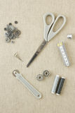 Sewing accessories in grey tones. Various sewing items, including scissors, tailors wheel, bobbins, spools of thread, measuring tape, thimble and buttons in Royalty Free Stock Photos