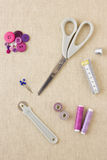 Sewing accessories in purple tones. Various sewing items, including scissors, tailors wheel, bobbins, spools of thread, measuring tape, thimble and buttons in Stock Photos