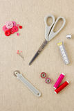 Sewing accessories in red and pink tones. Various sewing items, including scissors, tailors wheel, bobbins, spools of thread, measuring tape, thimble and buttons Royalty Free Stock Photo