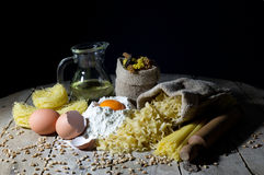 Various Shapes and Colors of Pasta and Ingredients for Pasta on Rustic Wooden Table, Black Background Royalty Free Stock Photos