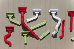 Various shapes and designs of colorful gutters displayed on wood wall. Royalty Free Stock Photos