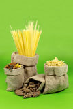 Various Shapes of Pasta In Jute Bags  on Green Stock Images
