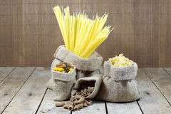 Various Shapes of Pasta In Jute Bags on Wooden Planks Stock Images