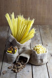 Various Shapes of Pasta In Jute Bags on Wooden Table Royalty Free Stock Photo