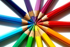 Colored pencils of various colors are making a circle against their heads. Various sharpened pencils are making their heads against each other and making a stock images