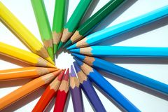 Colored pencils of various colors are making a circle against their heads. Various sharpened pencils are making their heads against each other and making a stock image
