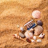 Various shells and small ship in bottle on sand. Background of various shells and small ship in bottle on sand. Top view Royalty Free Stock Photo