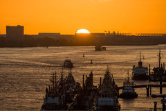 Various ships  in a harbor at sunset Royalty Free Stock Photos