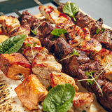 Various Shish Kebab. Chicken, Salmon and Meat Shish Kebabs on Parchment with Sauces royalty free stock photo