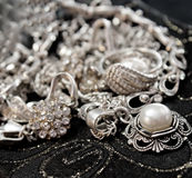 Various silver shining jewellery. And closeup pearl on black Stock Images