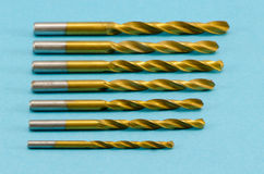 Various size golden drill bits on blue Stock Photo