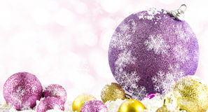 Various sized and colored Christmas balls with snow Royalty Free Stock Photos
