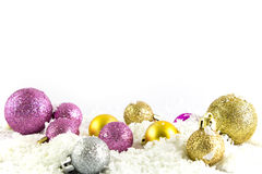 Various sized and colored Christmas balls with snow Stock Photography