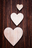 Various sized wooden hearts placed on a vintage wood Royalty Free Stock Photos